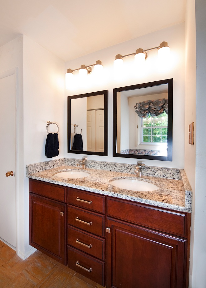 Client's Request: A Facelift for a Vanity - This small walk-through vanity area off the master bedroom needed a facelift.  Semi-custom cherry cabinets were chosen for their versatile storage drawers.   Want a quick bathroom update? Replace a large single mirror and long, horizontal light fixture with double mirrors and double lights.  Undermount sinks and single-lever faucets create a clean, contemporary feel.