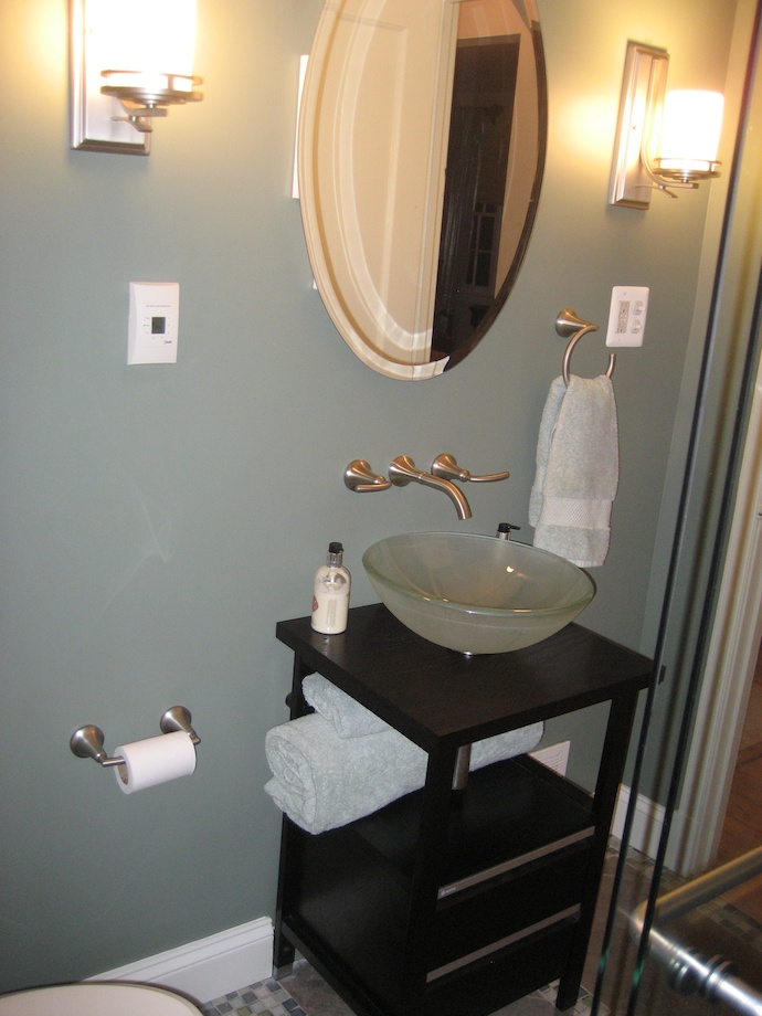 The wall-mount faucet makes it possible to use a small, shallow vanity in this tiny bathroom.