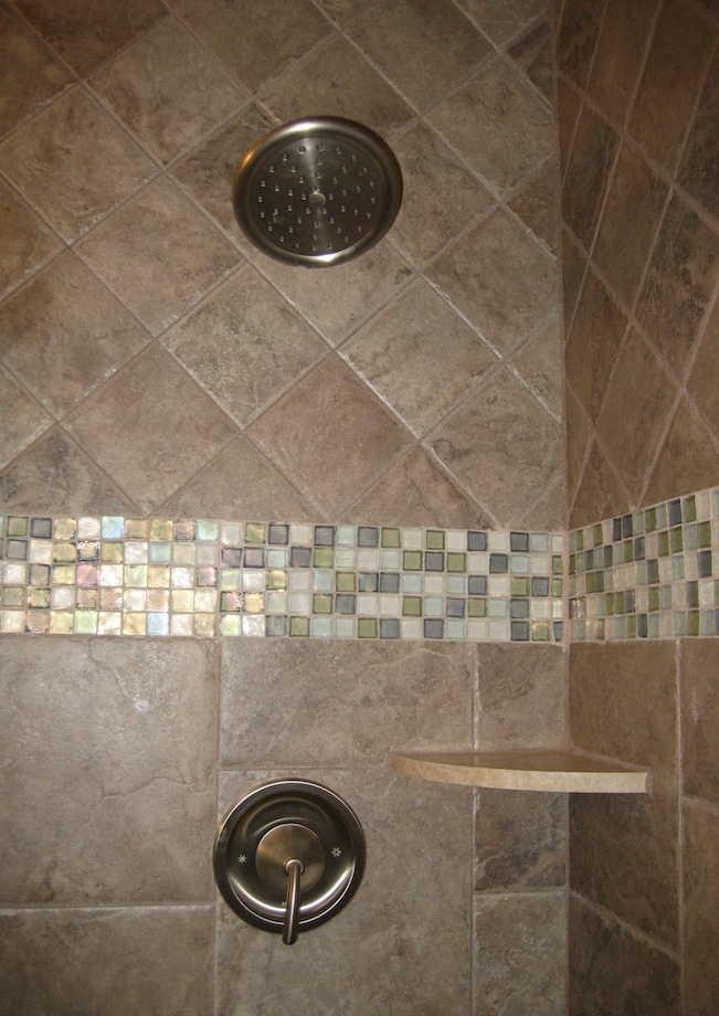 The use of different sizes and types of tiles in the shower creates eye-interest.
