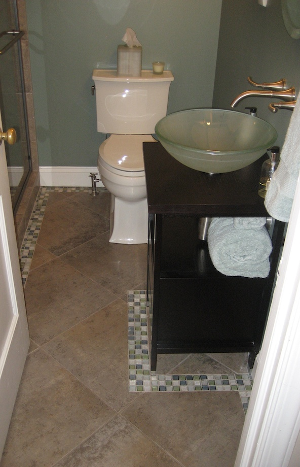 Client's Request: A Complete Bathroom Remodel - Large floor tiles make a small room seem bigger. Glass tile borders around the floor make it pop.