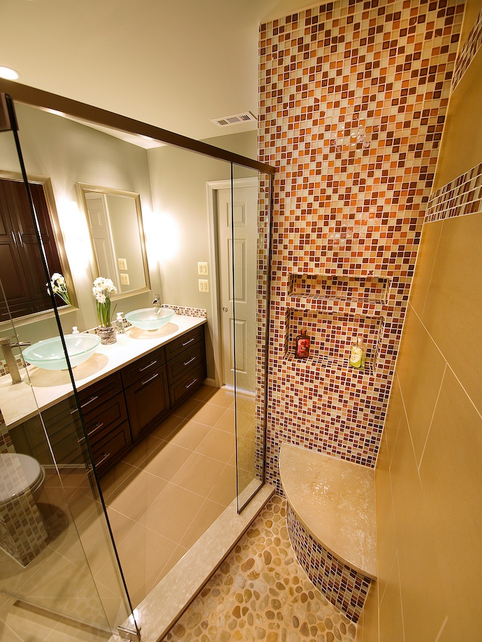 The top of the shower seat matches the marble of the vanity top.  Notice the niche for toiletries in the tiled shower wall.