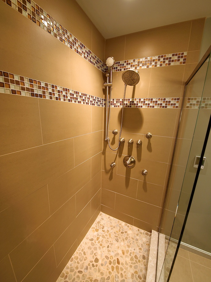 The pebble floor in shower adds more textural interest. The 12x24 wall tiles give the illusion of more space.
