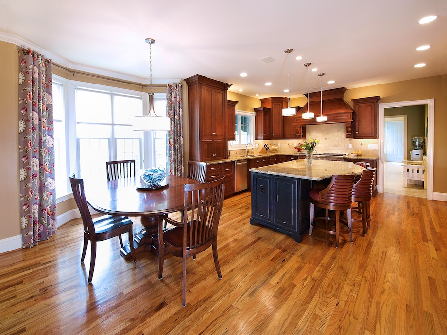 The large island and eating area is finished in black and rubbed through for contrast with the cherry cabinets. The cabinet closest to the windows holds an appliance garage with built-in electrical outlets.