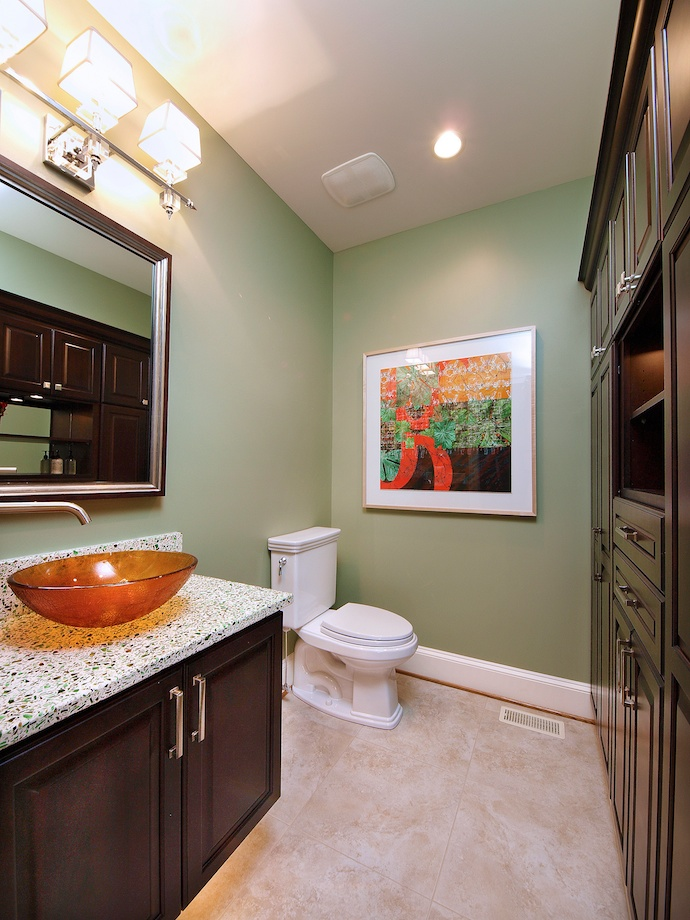 Client's Request: A Powder Room with Storage - This powder room is a new addition off the kitchen. An amber glass vessel sink looks dramatic against the recycled glass vanity top.