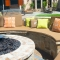 Custom cushions and pillows fit around the fire pit and endure the elements. The gas fire pit adds warmth and encourages community during the cool months. An eleven-foot umbrella shields from sun or rain during the summer.