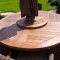The 60-inch custom teak table features a lazy Susan. With a little teak oil, the natural wood tones will endure without taking on a gray patina.